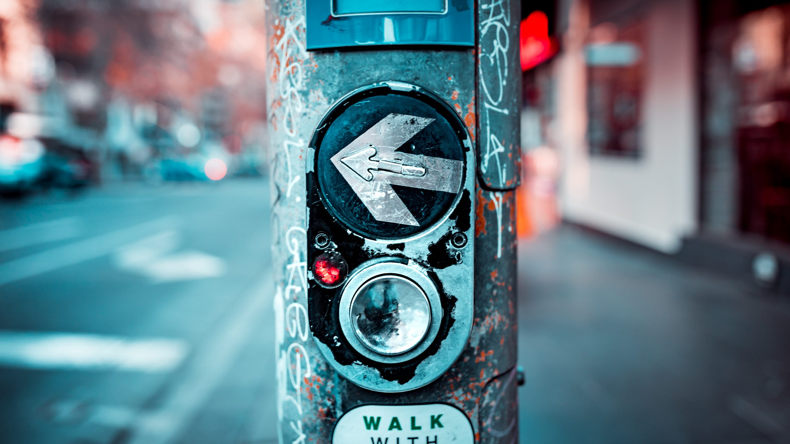 Picture of a pedestrian walking button in urban Melbourne pointing left on a