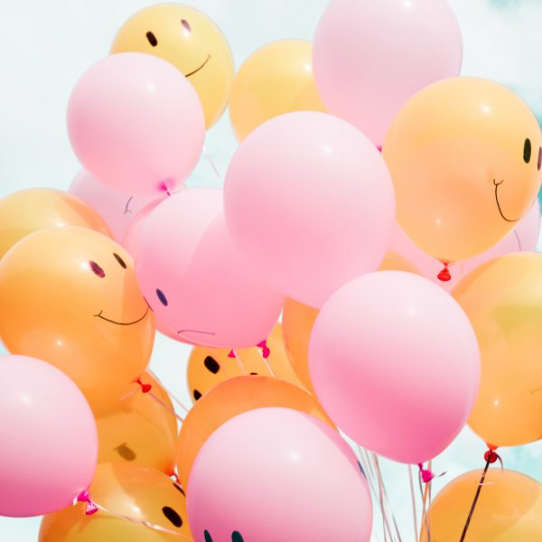 Picture of smiling and frowning balloons in the air, celebrating the many Melbourne school holidays activities happening around the city