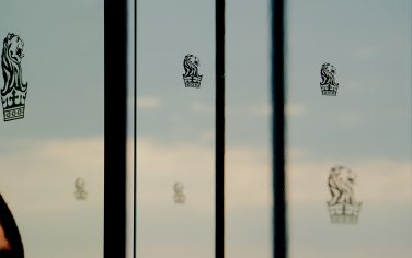 Picture of a window with clouds in the background and a Ritz Carlton Melbourne decal sticker in the foreground