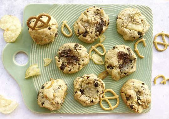 Green ceramic tray with a spread of gluten-free cookie recipes with chips and pretzels surrounding them