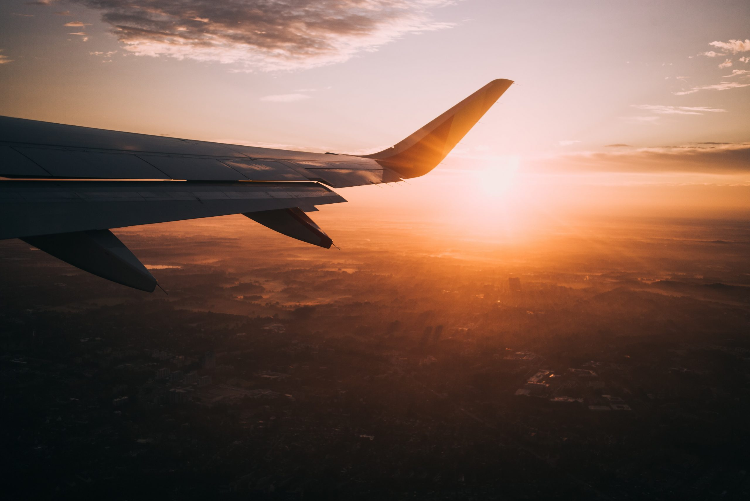 Picture of a plan wing in the sunset, signifying the Australian international borders opening